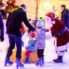 Father Christmas on an ice rink with 2 children and 1 adult