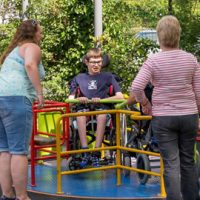 Young person on a wheelchair accessible roundabout