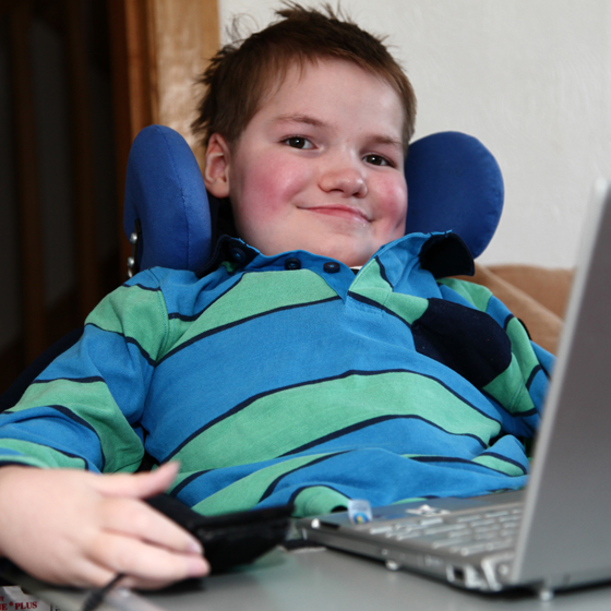 Boy in electric wheelchair with laptop