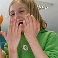 Girl laughing with hands in front of face