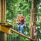 Two adults and child on tree top activity course at Go Ape.