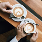 hands holding coffee mugs from above