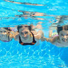 Three young people swimming under water.