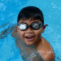 Little boy with goggles in pool