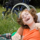 Disabled girl laughing with mum in field