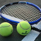 Close up of tennis racquet and two tennis balls.
